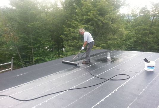 roofing contractor applying waterproofing to the roof